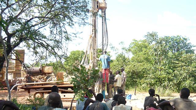 Brunnenbau mit schwerem Gerät und vielen Helfern.