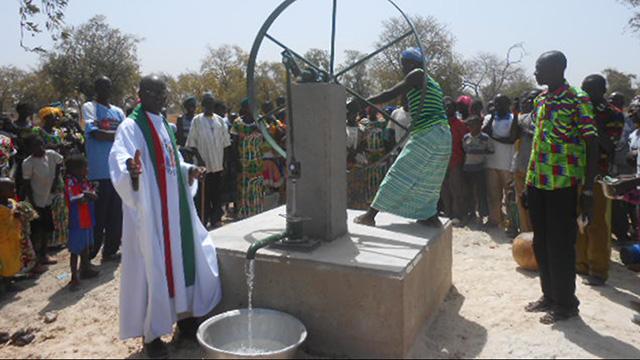 Der neue Brunnen wird geweiht, eine afrikanische Frau dreht das Wasserrad.