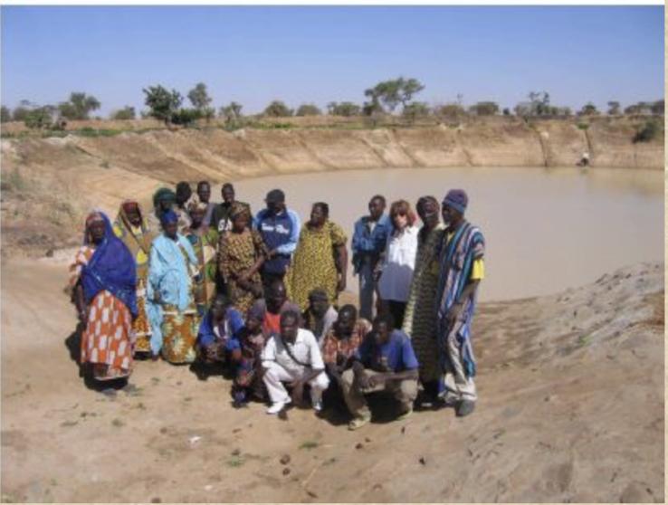 Eine Gruppe Einheimischer steht vor einem kleinen See.