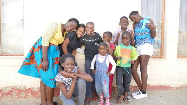 Neun Personen, darunter acht Kinder, stehen vor ihrem neuen Steinhaus. Sie lachen.
