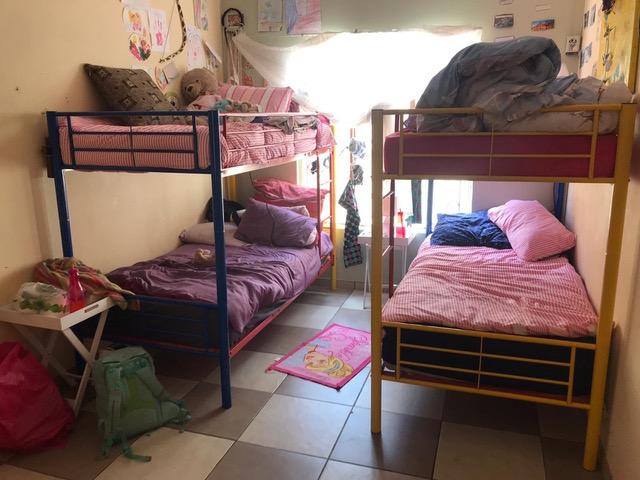 Zwei Hochbetten aus Eisengestellen und ein paar persönliche Dinge stehen in einem kleinen Kinderzimmer.